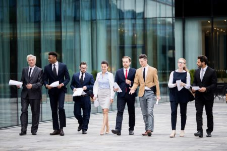 Several business people in elegant suits walking by modern building while having talk with each other